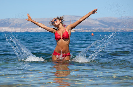 Beautiful bikini model splashing water  photo