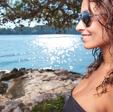 Sexy woman in white bikini near edge of infinity pool looking far on horizon. photo