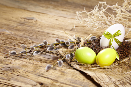 Easter basket with Easter Eggs on wooden background. photo