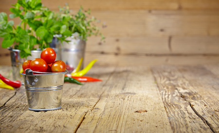Tomatoes, chives and chili peppers on a wooden table top  photo