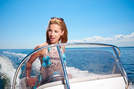 boat motor: Summer vacation - young girl driving a motor boat