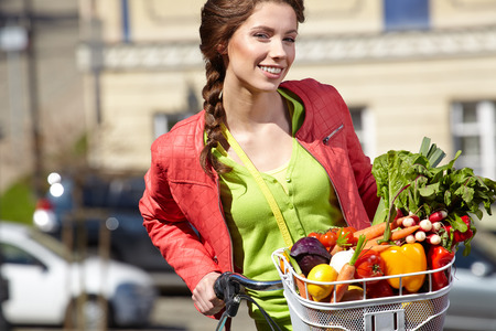 pretty young woman: Pretty young woman with bicycle and groceries in old town street  Stock Photo