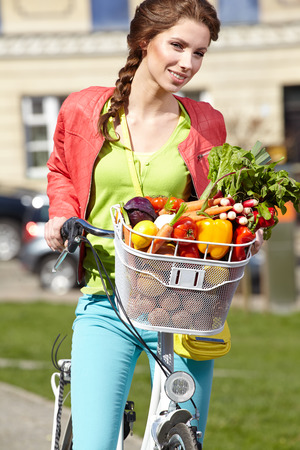 Pretty young woman with bicycle and groceries in old town street  photo