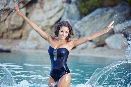Beautiful young woman in bikini on the beach splashing water