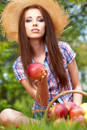 Smiling Young Woman Eating Organic Apple in the Orchard.Basket of Apples.  photo