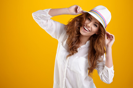 toothy smile: Young Woman with spring hat against yellow background