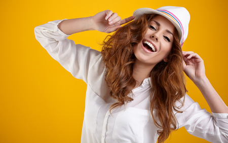Young Woman with spring hat against yellow background  photo