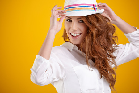 Fashion portrait of pretty woman wearing stylish hat. Young Caucasian female model posing in studio over orange  background.  photo