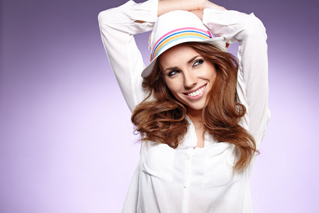 Fashion portrait of pretty woman wearing stylish hat  Young Caucasian female model posing in studio over violet  background   photo