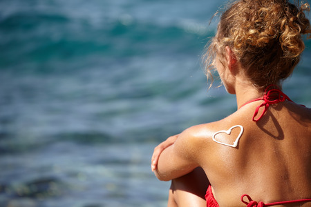 sun lotion: teenage girls back with sunburn and heart of sun lotion
