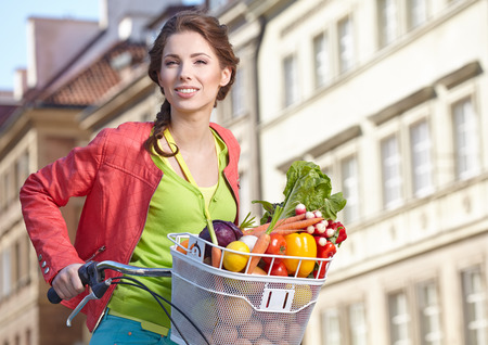 Pretty spring  woman with bicycle and groceries in old town street   photo
