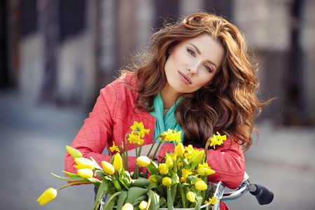 sensual brunette girl sitting on bicycle with some spring flowers in the basket  photo