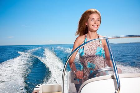 Summer vacation - young girl driving a motor boat Фото со стока - 27997041