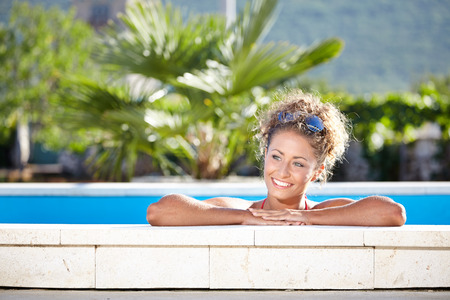 Portrait of a sexy woman relaxing in a swimming pool photo
