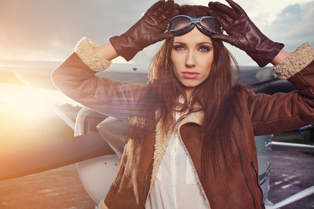 aircrew: Portrait of young beautiful woman pilot in front of airplane. Stock Photo