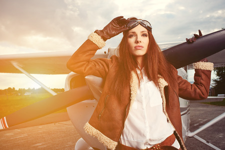 aircrew: Portrait of young beautiful woman pilot in front of airplane.