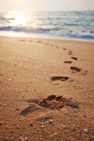 huella pie: Huellas en la sand.Traces de playa en la playa. Pasos en la playa por el mar en verano Foto de archivo