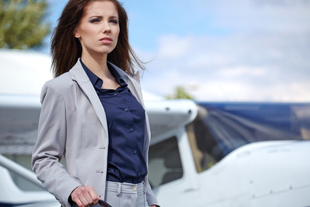 Young beautiful businesswoman  in front of airplane. photo