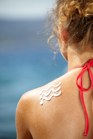 sun lotion: girl back with sunburn and wave of sun lotion
