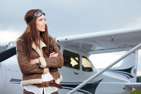 Portrait of young beautiful woman pilot in front of airplane.  photo