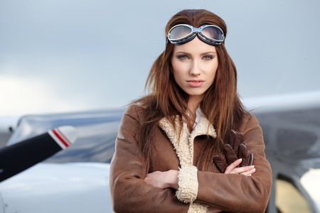 Portrait of young beautiful woman pilot in front of airplane   photo