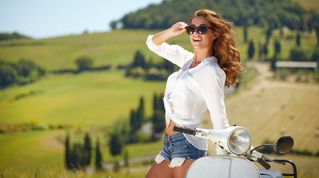 Young beautiful italian woman sitting on a italian scooter in tuscany outdoor photo