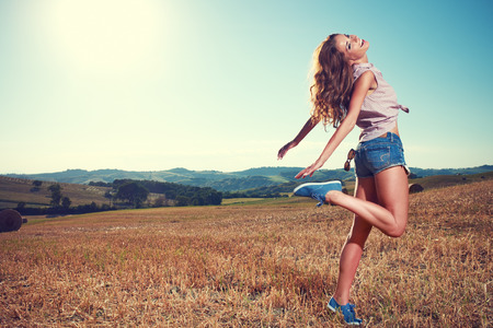 Girl walking on the field in the countryside photo