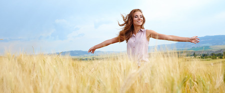 looking up: Happy woman in golden wheat