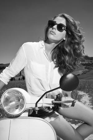 beautiful italian woman sitting on a italian scooter.  photo