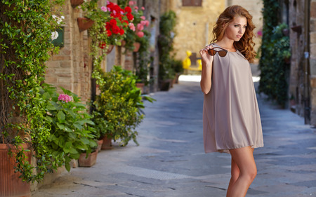 beautiful woman in summer dress walking and running joyful and cheerful smiling in Tuscany, Italy.  photo