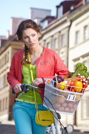 Pretty spring  woman with bicycle and groceries in old town street.  photo