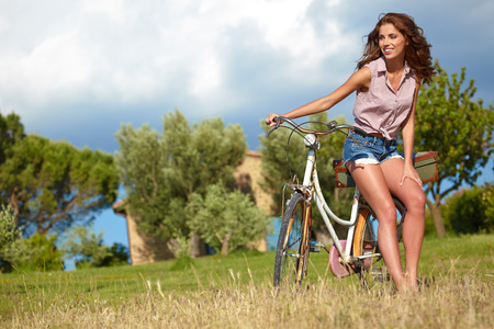 Sexy woman with vinntage bike in a country road. photo