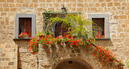 balcony window: Colorful flowers lining a medieval stone wall in Italy Stock Photo