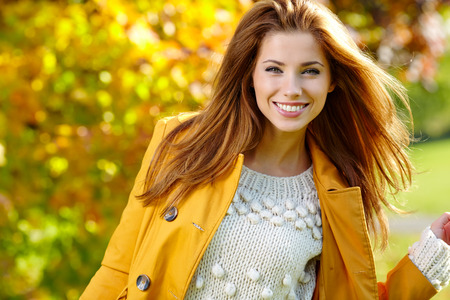 femmes souriantes: Belle femme élégante debout dans un parc à l'automne Banque d'images
