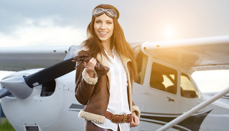 model airplane: Portrait of young beautiful woman pilot in front of airplane.