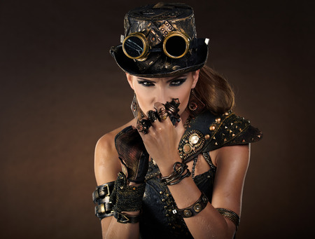 punk rock: Portrait of a beautiful steampunk woman over smoke background.  Stock Photo