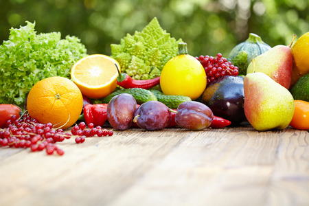 Fresh organic vegetables ane fruits on wood table  in the garden  photo