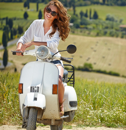tuscany: Young beautiful italian woman sitting on a italian scooter in tuscany outdoor