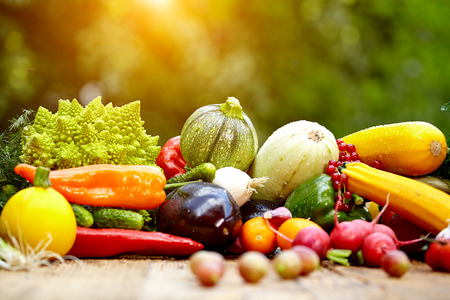 balanced diet: Fresh organic vegetables ane fruits on wood table  in the garden  Stock Photo