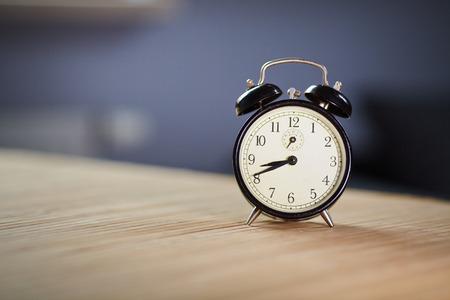 Retro alarm clock on desk front grey wall background  photo