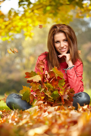 Fall woman- Autumn portrait of happy lovely and beautiful young woman in forest in fall colors. Stock Photo