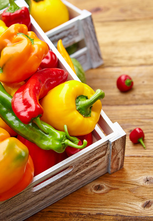 Colorful peppers in a wooden box photo