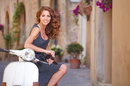 Young beautiful italian woman sitting on a italian scooter   photo