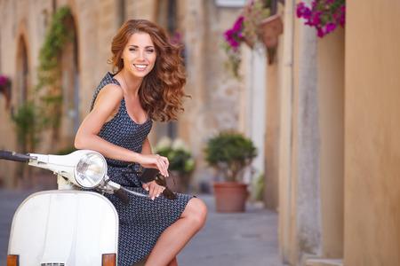 Young beautiful italian woman sitting on a italian scooter   photo