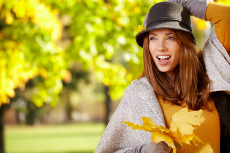 Young woman with autumn leaves in hand and fall yellow maple park   photo