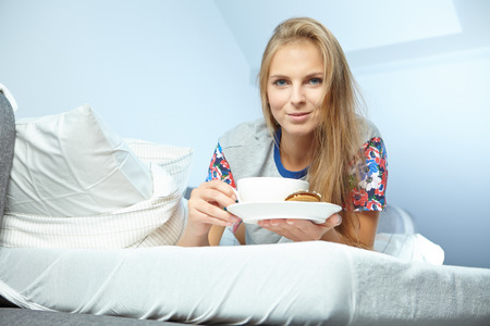 Attractive woman with a cup of coffee on the bed  photo