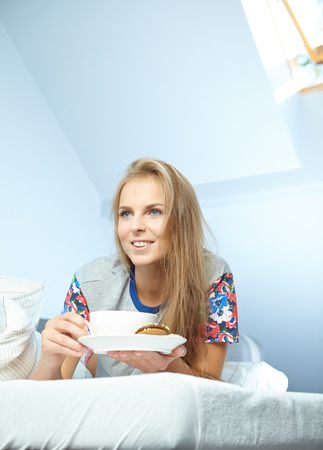 head rest: Attractive woman with a cup of coffee on the bed  Stock Photo