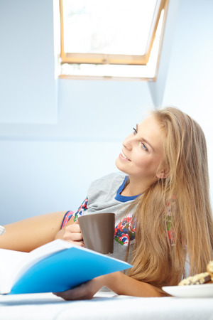 Young beautiful woman reading book  in bed photo