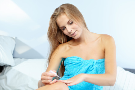 finger tip: beautiful woman applying red nail polish in bed at home Stock Photo