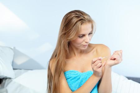 beautiful woman applying red nail polish in bed at home photo